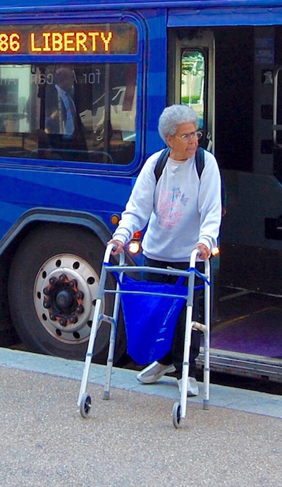Woman with walker exiting a public transportation bus