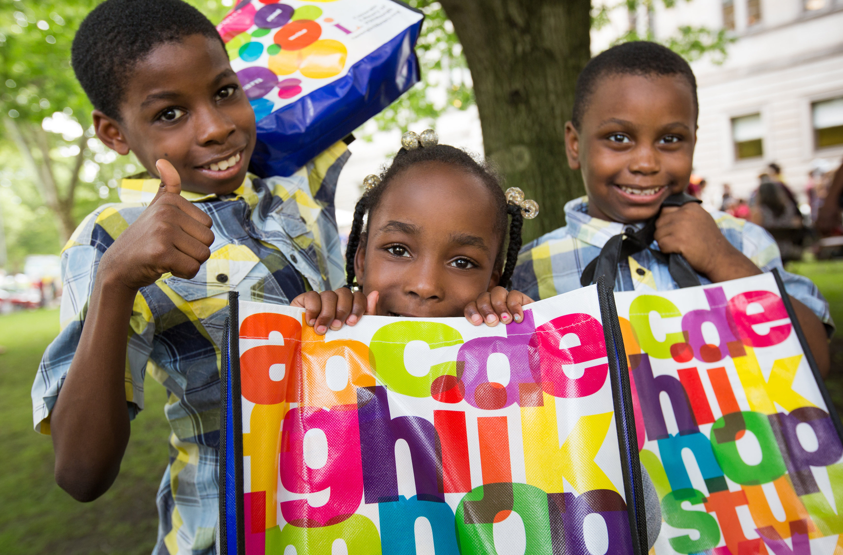 Three school children outside Carnegie Library of Pittsburgh, smiling and holding bags with colorful alphabet letters on them.