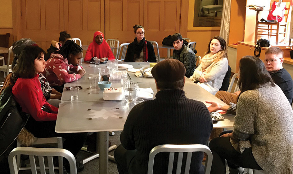 High school student refugees in discussion around a large table at City Theatre.